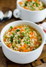 Insanely simple barley soup in a white bowl with carrots and green onions on top