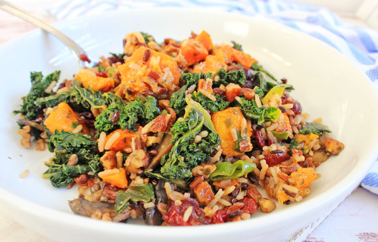 Front view of white bowl filled with harvest wild rice, sweet potatoes, kale and a light glaze