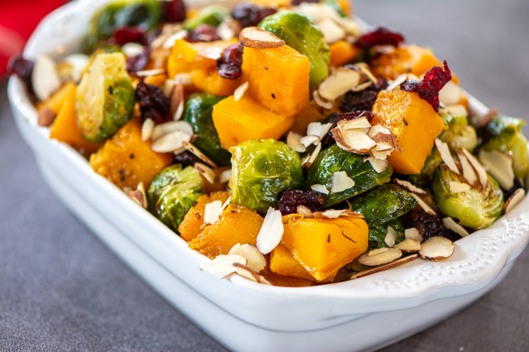 Roasted Brussel Sprouts and Squash in a white ceramic dish with cranberries and almonds