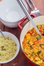 Mediterranean Vegetable Casserole in a dutch oven with couscous and white bowls