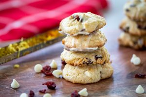 pile of lightly glazed cookies on a cutting board with white chocolate chips and cranberries sprinkled. A zester with citrus rind in the background