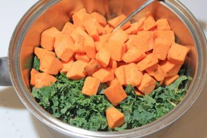 bowl with spoon and uncooked sweet potatoes and kale