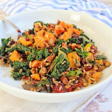 delicious bowl of the kale and sweet potato salad mixed in with wild rice on a white cutting board