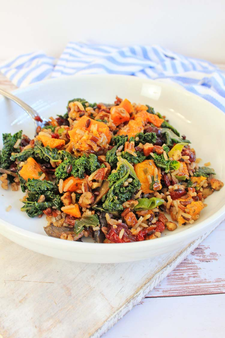 delicious bowl of the kale and sweet potato salad mixed in with wild rice on a white cutting board.