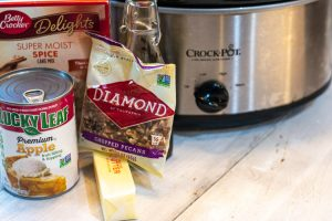Slow Cooker and the ingredients to make the apple dump cake on a white board