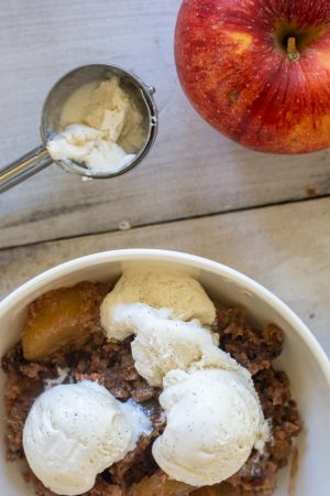 top down view of a bowl of ice cream topped apple dump cake with the ice cream scoop in the background