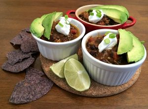 three small ramekins of black bean chili topped with sour cream, avocado and two limes and blue corn chips on a trivet