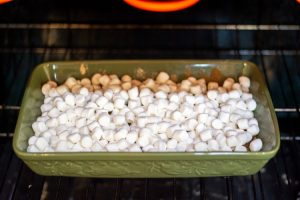 green pan in the oven with the cake mix and topped with marshmallows ready to be broiled