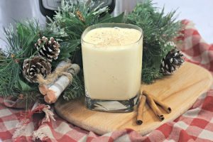 Instant Pot Eggnog is the perfect holiday treat. Glass on a cutting board with cinnamon sticks and nutmeg