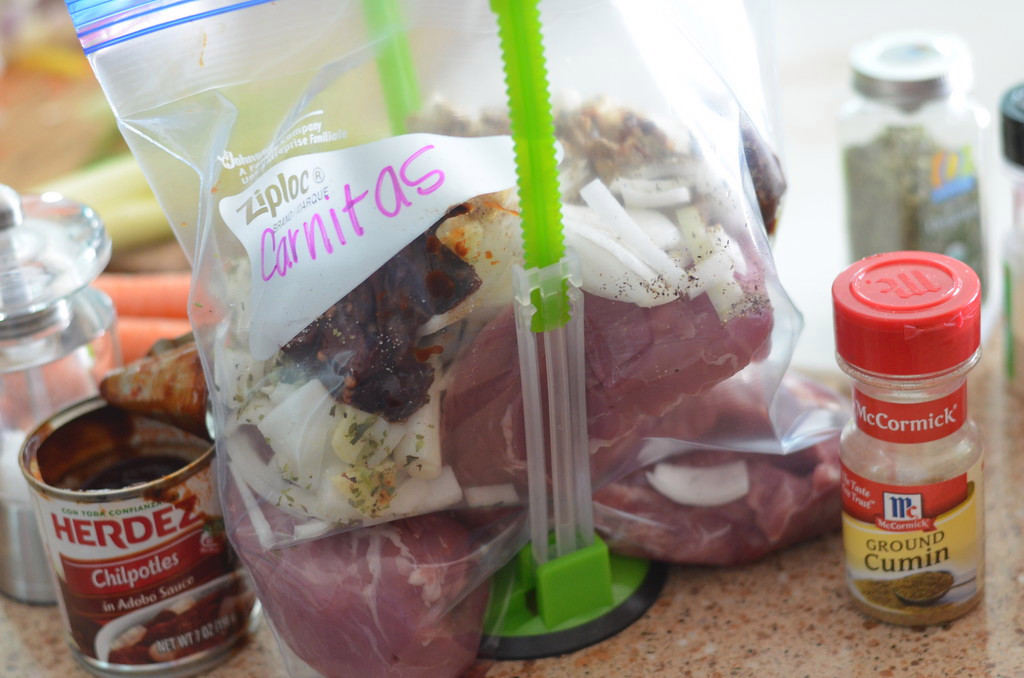 bag of carnitas with all the fixings and labeled. Around the bag are the ingredients that were added including chipotles