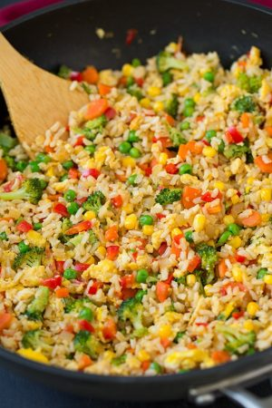 Red peppers, corn, broccoli and eggs mixed in Vegetable Fried rice in a wok with a wooden spoon