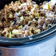 crock pot filled with the wild rice stuffing, apples, sausage and cranberries