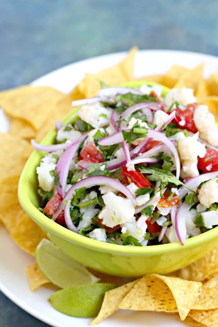 Fun cauliflower ceviche in a lime green bowl topped with red onions, limes, red peppers and chips on a plate