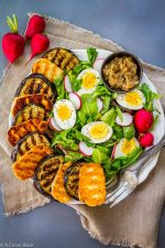 Grilled Eggplan and Halloumi surrounding lettuce, boiled eggs and radishes