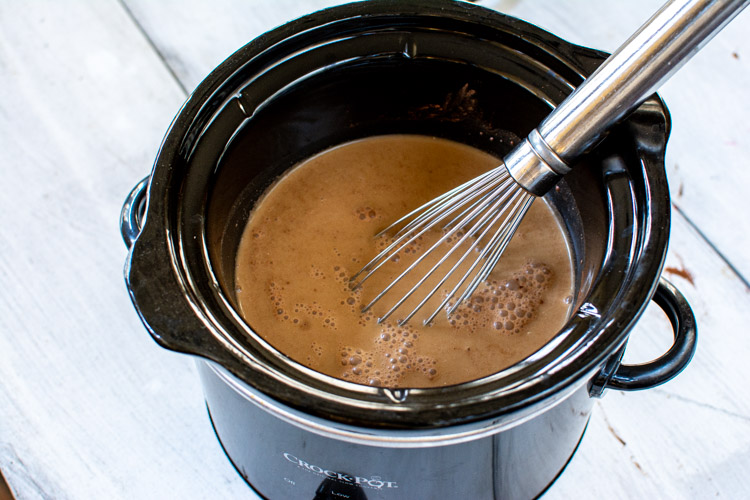 small slow cooker with coffee, cocoa powder and cream.