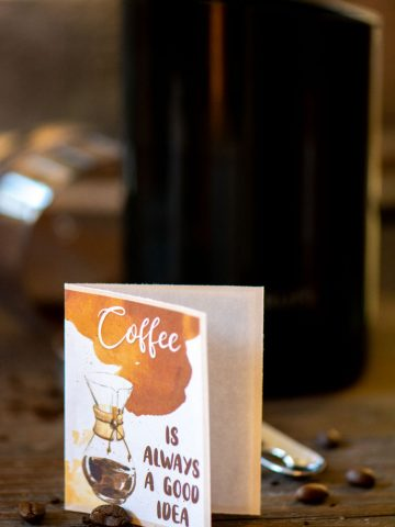 coffee is always a good idea notecard on a table with coffee beans and a grinder