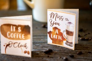 two free coffee card printables on a table with a coffee cup in the background