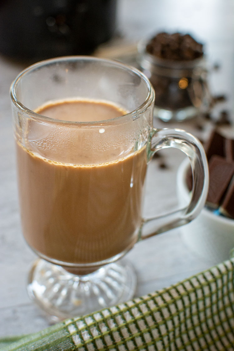 Hot cup of Irish Coffee in a glass with coffee beans and a small crock pot in the background.