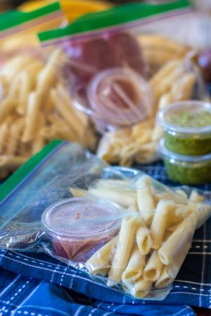 ziplock bags filled with frozen pasta and cups of sauce on a blue cloth napkin