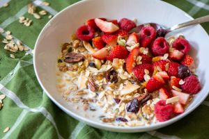 healthy muesli in a bowl for breakfast with fresh fruit on a green napkin