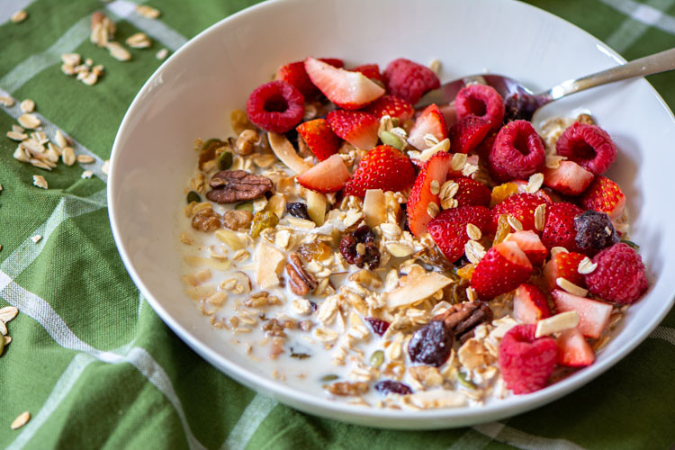 healthy muesli in a bowl for breakfast with fresh fruit on a green napkin.