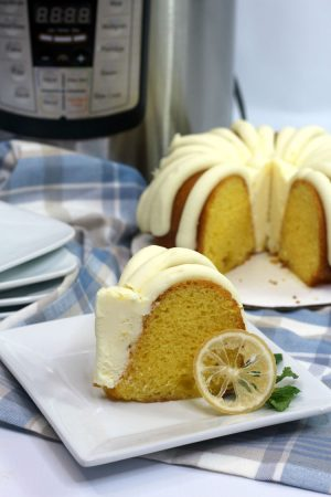 Slice of bundt cake with a lot of icing on a plaid cloth with the instant pot in the background
