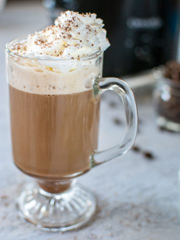 Glass filled with baileys coffee and topped with whipped cream and sprinkled with chocolate shavings