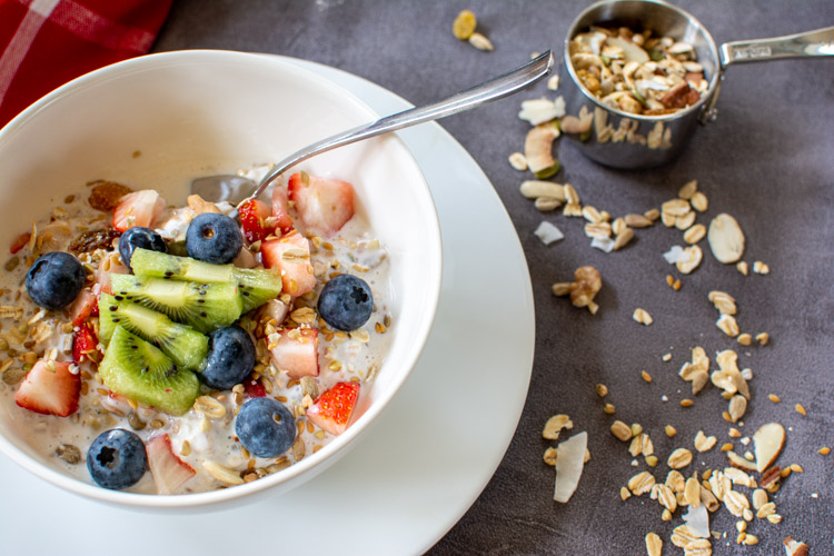 Bowl of overnight muesli topped with fresh blueberries, strawberries and kiwi on a tablecloth with sprinkled muesli.