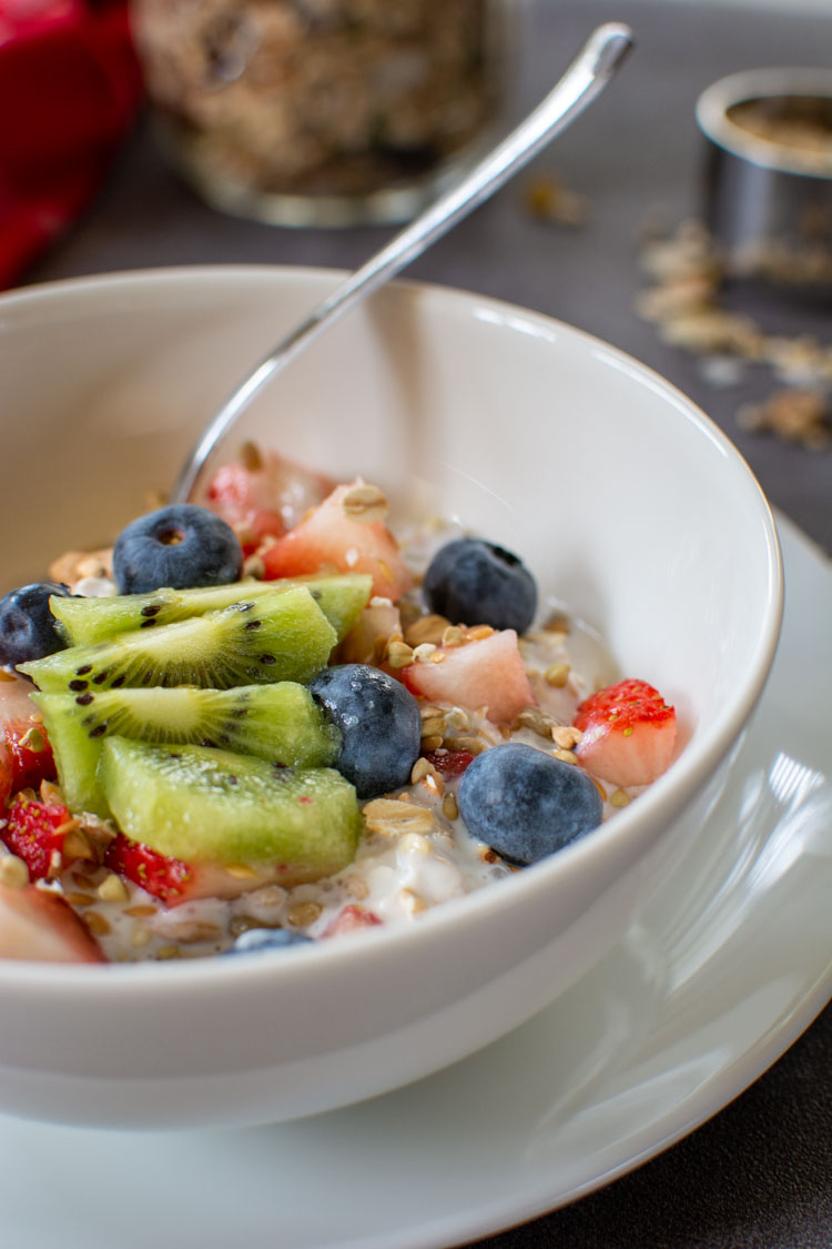 huge blueberries, kiwi and strawberries are chopped on top of the overnight muesli with a spoon in the white bowl.