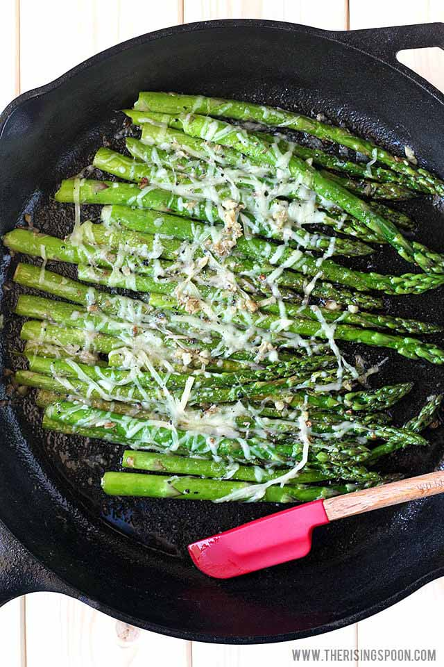 Several spears of low carb asparagus in a cast iron skillet with parmesan and garlic