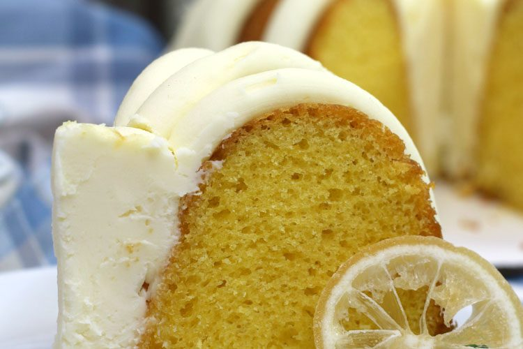 Slice of Lemon Bundt Cake with thick icing and a slice of lemon on a white plate with the instant pot in the background