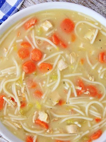 Top down view of a white bowl with the delicious chicken soup filled with carrots and noodles