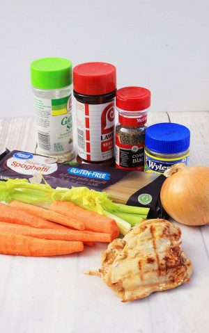 All of the ingredients needed for the chicken soup on a white wooden board