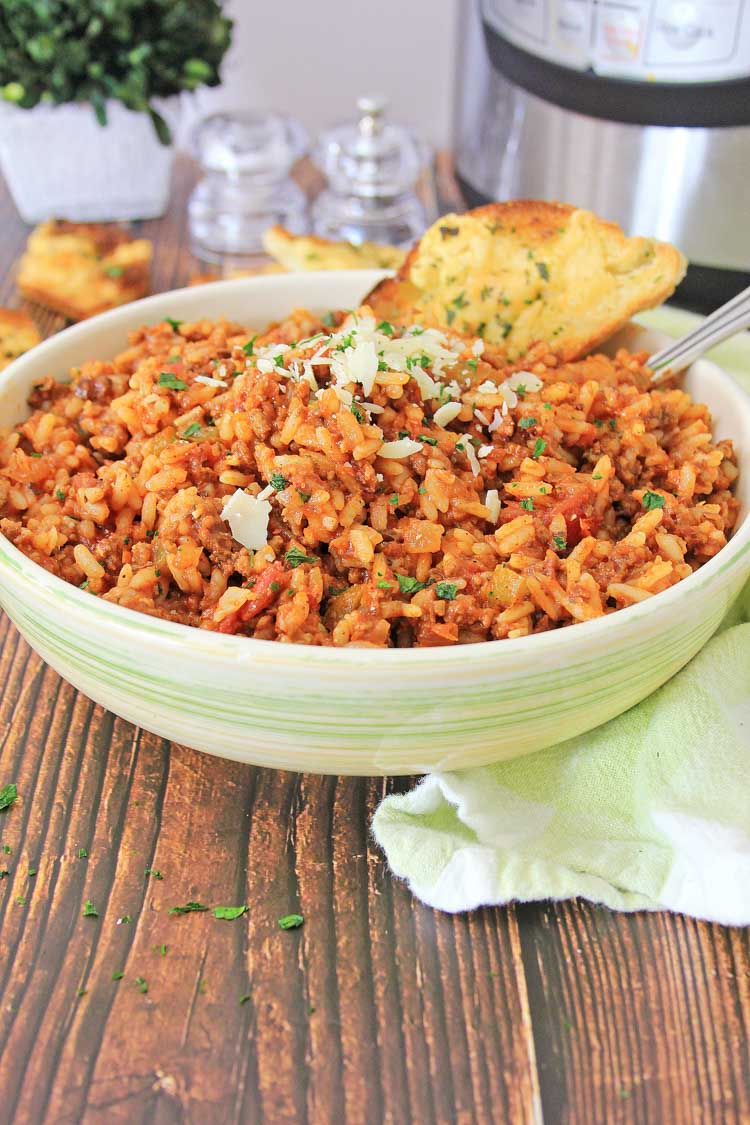 bowl of instant pot spanish rice with garlic bread and a spoon in the bowl and instant pot in the back.