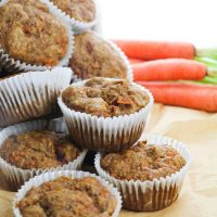 freshly baked carrot muffins in a stack with carrots behind them