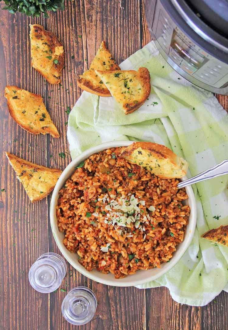 bowl of spanish rice and instant pot on a green cloth napkin with toasted bread.