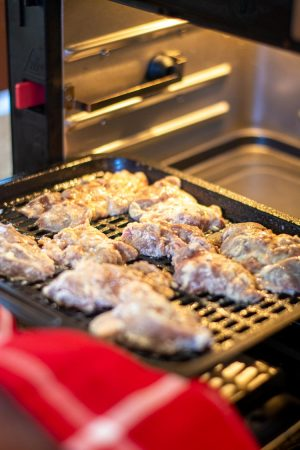Adding a tray of coated chicken livers to the air fryer