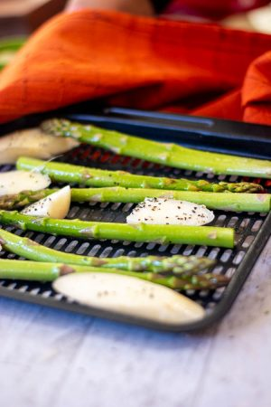 salt and pepper on the asparagus on the tray and ready for the air fryer