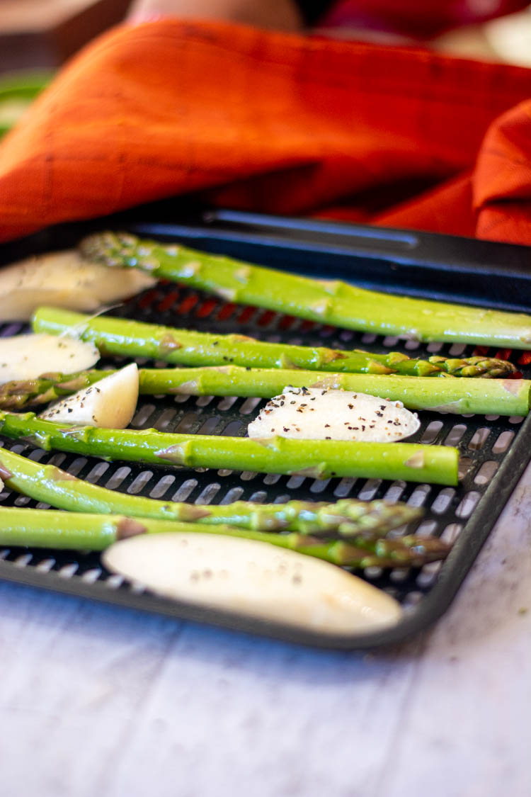 salt and pepper on the asparagus on the tray and ready for the air fryer.