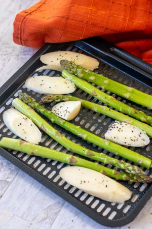 air fryer tray with green asparagus spears and sliced white asparagus coated with a bit of salt and pepper