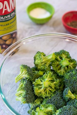 glass bowl with freshly cut broccoli florets and salt and pepper in the background with a bottle of spray olive oil