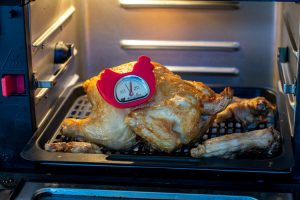 Cooked Cornish Hen in the Air Fryer with a temperature gauge to show it is fully cooked