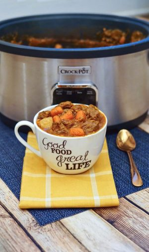 Mug filled with hearty beef stew on a yellow cloth napkin and the slow cooker in the background