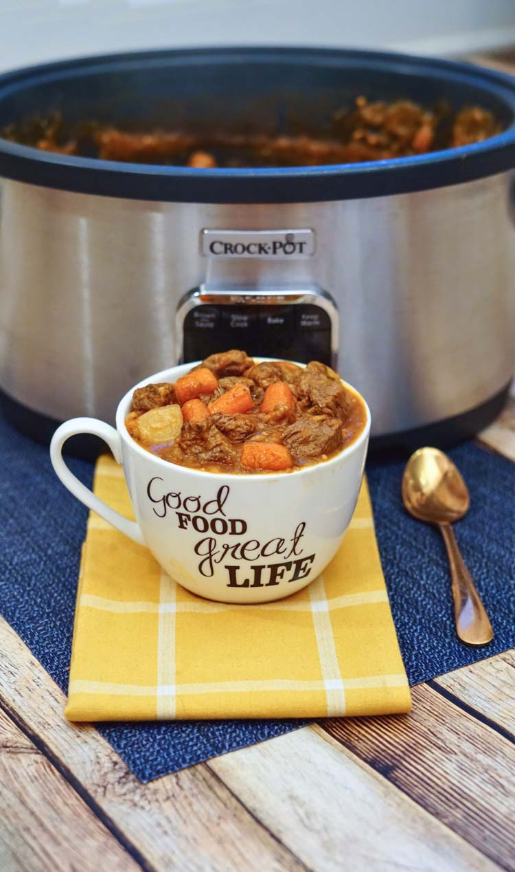 Mug filled with hearty beef stew on a yellow cloth napkin and the slow cooker in the background.