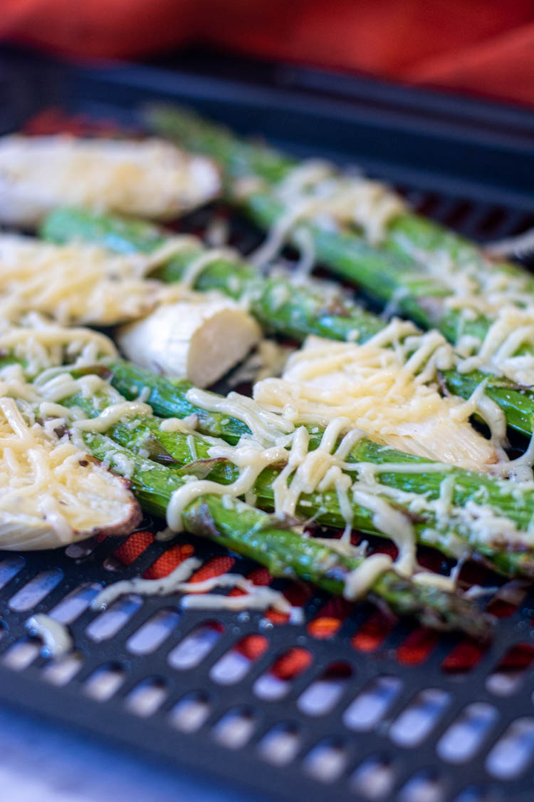 Grated parmesan melting over the asparagus on an air fryer tray.