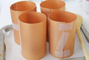 after cutting, tape the copper mats into cylinders and sitting on parchment paper with a wooden spoon