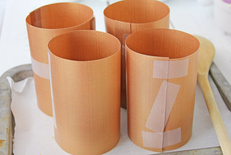 after cutting, tape the copper mats into cylinders and sitting on parchment paper with a wooden spoon.
