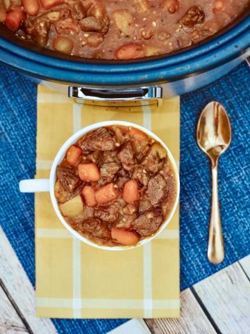 closeup of the crockpot beef stew in a cup on a blue and yellow cloth