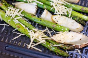 after roasting, the asparagus is quickly topped with parmesan