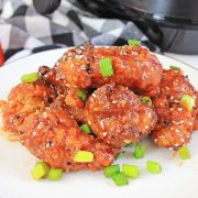 pile of chicken wings and green onions on a white plate in front of the air fryer